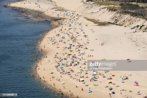 TOPSHOT People enjoy the beach on the bassin d'Arcachon on August 4 2018 in Arcachon southwestern France