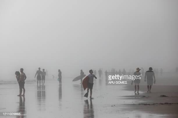 People enjoy the beach through the afternoon fog amid the novel coronavirus pandemic in Huntington Beach California on April 25 2020 Orange County is...