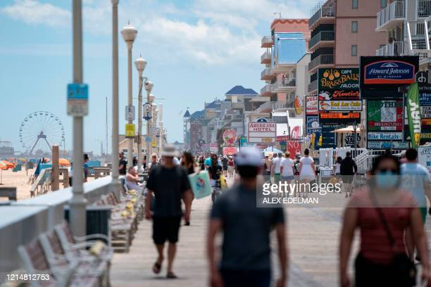 People enjoy the boardwalk during the Memorial Day holiday weekend amid the coronavirus pandemic on May 23 2020 in Ocean City Maryland The beach...