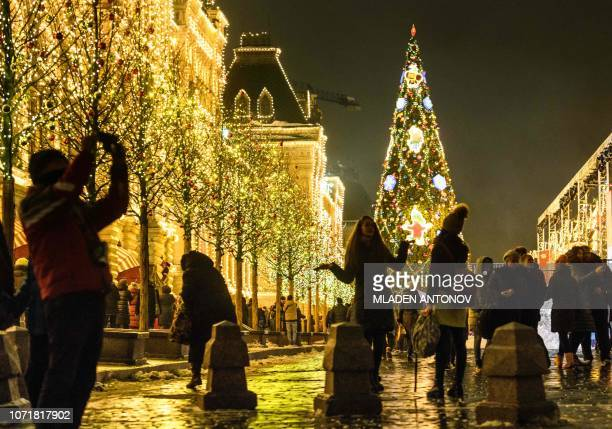 People enjoy the Christmas and New Year decoration in front of GUM department store on the Red Square in Moscow on December 11 2018