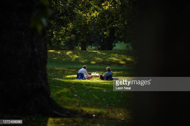 People enjoy the early evening sun while respecting the new group size limitations, as they relax in the park on September 14, 2020 in London, United...