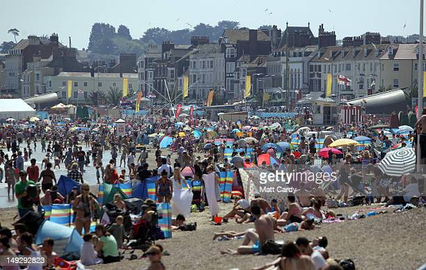 People enjoy the fine weather as they gather on the beach as Weymouth gears up to host the London 2012 sailing events which start this weekend on...