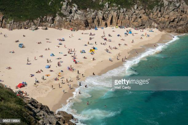People enjoy the fine weather as they spend time on the beach at Porthcurno Beach near Penzance on June 28, 2018 in Cornwall, England. Parts of the...