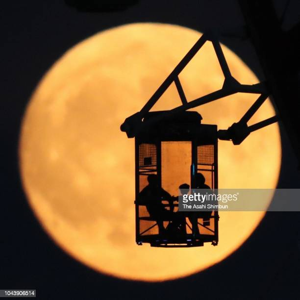 People enjoy the harvest moon from a Ferris wheel on September 24 2018 in Tokyo Japan