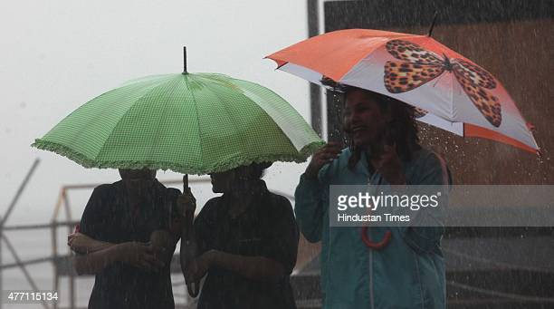 People enjoy the heavy rain on June 14 2015 in Mumbai India Heavy rains caused major water logging in many areas leaving residents and commuters...