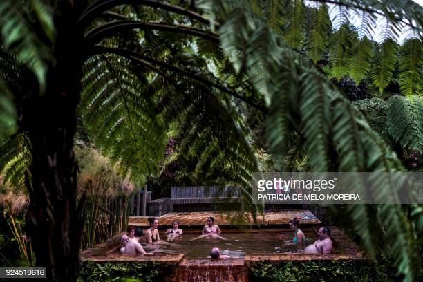 People enjoy the hot springs at Poca da Dona Beija Furnas in Sao Miguel island Azores Portugal on February 22 2018 / AFP PHOTO / PATRICIA DE MELO...