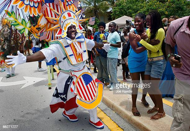People enjoy the Junkanoo parade as a dancer passes by at the Goombay Festival on June 6 2009 in Coconut Grove Florida The festival is a celebration...