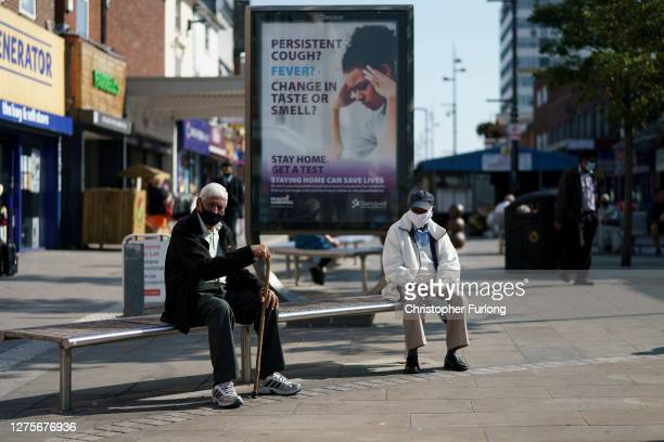 People enjoy the last fo the Summer sunshine as they wear protective face masks in the High Street on September 22, 2020 in West Bromwich, United...