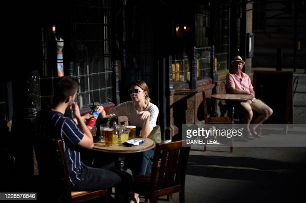 People enjoy the late afternoon sunshine as they sit outside of a pub in central London on September 18, 2020. - Millions more people in northern and...