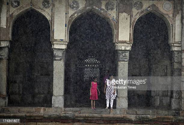 People enjoy the Monsoon rain inside the Humayun Tomb on July 24 2013 in New Delhi India The minimum temperature settled a notch below average at 259...