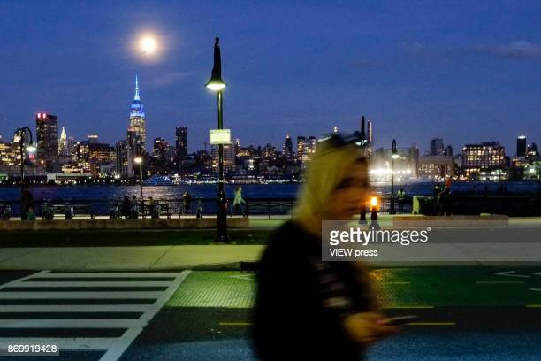 People enjoy the moonrise over the Empire State Building and Manhattan skyline along the Hudson river on November 2 2017 in Hoboken NJ