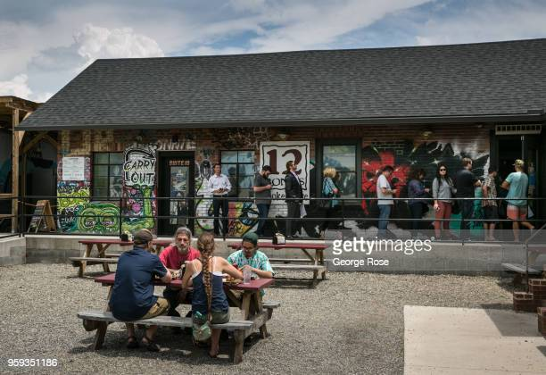 People enjoy the outside patio at 12 Bones Smokehouse barbecue restaurant in the River Arts District on May 11 2018 in Asheville North Carolina...