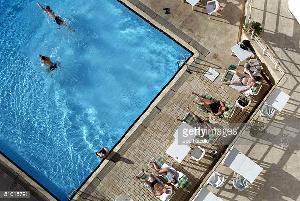 People enjoy the pool at the Al Hamra hotel July 1 2004 in Baghdad Iraq A defiant Saddam Hussein apeared in Iraqi court July 1 and rejected charges...