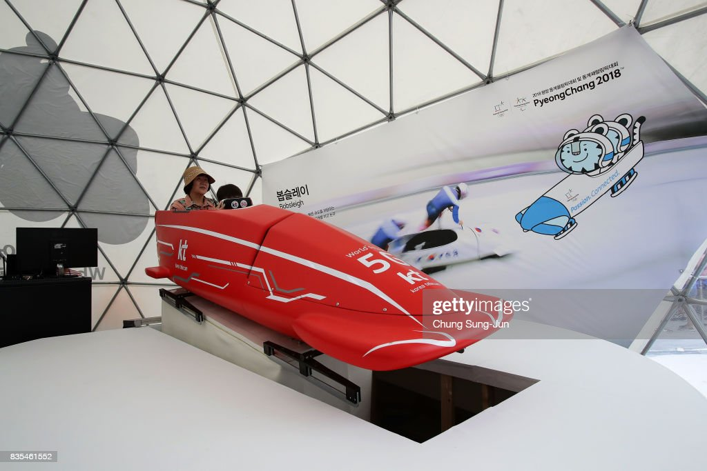 People enjoy the PyeongChang Winter Olympics booth next to 'Bobsleigh In the City' event on August 19, 2017 in Seoul, South Korea. The 22-metre-high 300-metre-long water slider has been set up in the central Seoul to promote upcoming PyeongChang Winter Olympics.