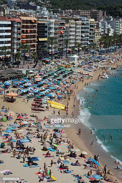 People enjoy the sea and beach in the Catalonian coastal city of Lloret de Mar along the Mediterranean sea on August 7 2016 / AFP / JOSEP LAGO