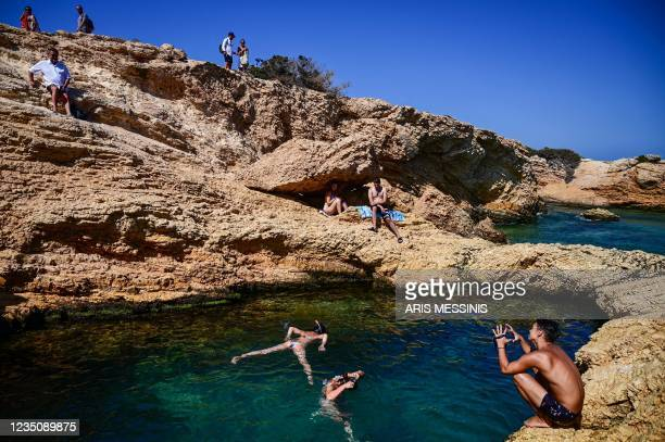 People enjoy the sea at the small Aegean island of Koufonisi at the chamber of Cyclades on September 6, 2021.