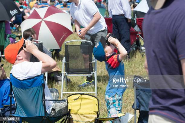 People enjoy the show during the Royal International Air Tattoo at RAF Fairford on July 12, 2014 in Fairford, England. The Royal International Air...