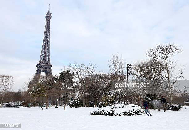 People enjoy the snow on the ChampdeMars near the Eiffel tower on March 13 2013 in Paris Blizzardlike conditions coming only eight days before the...