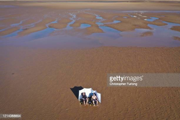 People enjoy the Spring sunshine as they keep their social distance on a deserted Blackpool beach on March 22 2020 in Blackpool England Many of the...