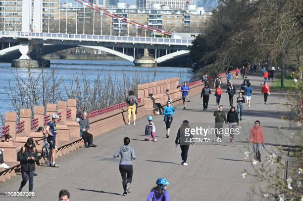 People enjoy the spring sunshine in Battersea Park in London on March 24 2020 after Britain's government ordered a lockdown to slow the spread of the...