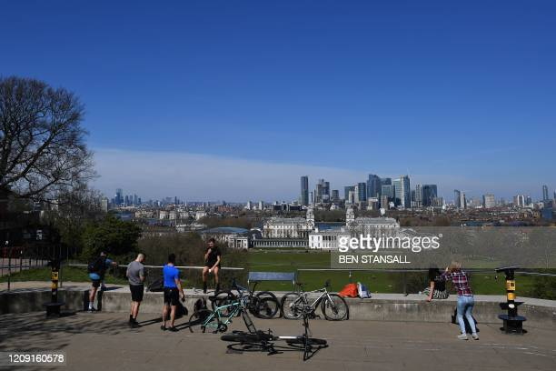 People enjoy the Spring sunshine in Greenwich Park in London on April 5 as the warm weather tests the nationwide lockdown to combat the novel...