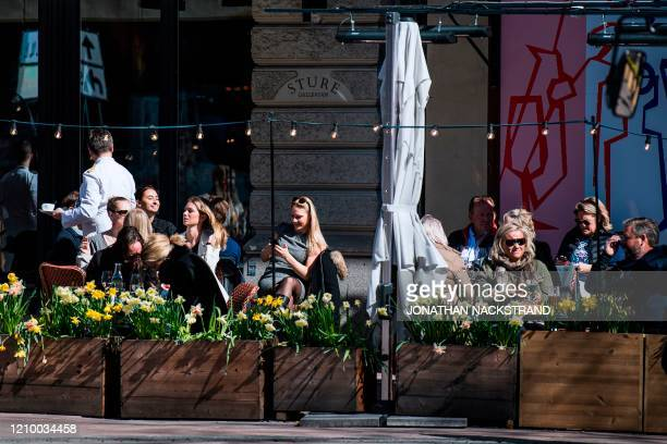 People enjoy the spring weather as they sit at a restaurant in Stockholm on April 15 during the coronavirus COVID-19 pandemic.