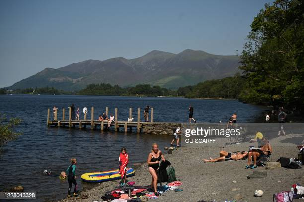 People enjoy the summer sunshine beside Derwentwater in the Lake District in north west England on August 14 as many people take advantage of the...