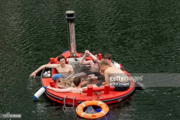 People enjoy the sun and the warm weather in a Skuna Hot Tub Boat on the London North dock at Canary Wharf.