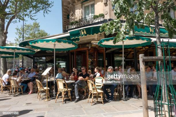 People enjoy the sun and warm spring temperatures at the terrace of the French cafe quotLes deux magotsquot at the SaintGermaindesPres district in...