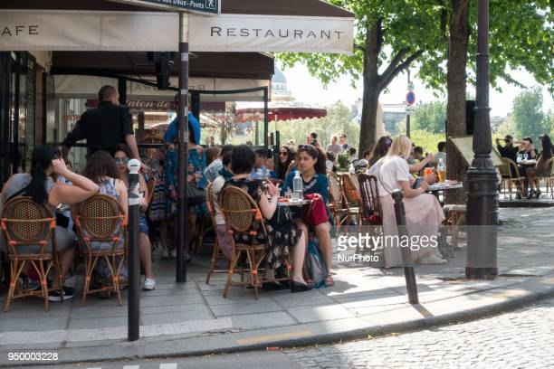 People enjoy the sun and warm spring temperatures at the terrace of the Berthillon cafe at the IleSaintLouis in Paris district in Paris on April 22...