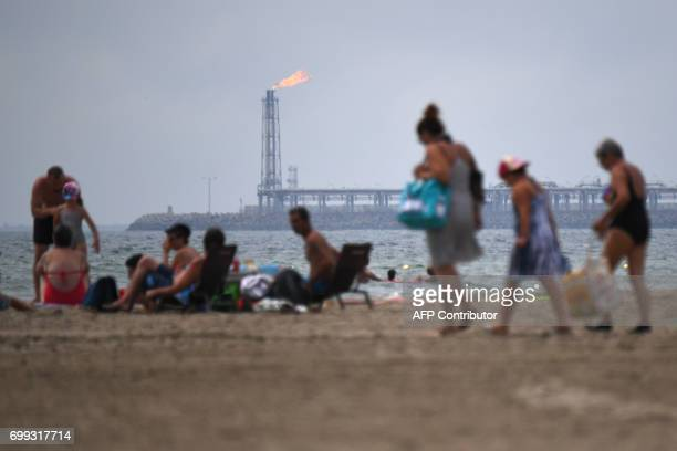 People enjoy the sun at a beach in FossurMer southern France on June 21 as fumes rise from the chimneys of a refinery plant in the background The...
