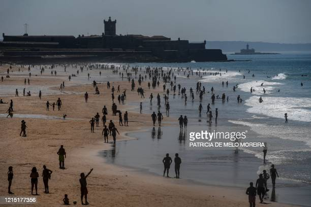 TOPSHOT People enjoy the sun at Carcavelos beach in Cascais in the outskirts of Lisbon on May 26 2020 as temperatures rise and the Portuguese...