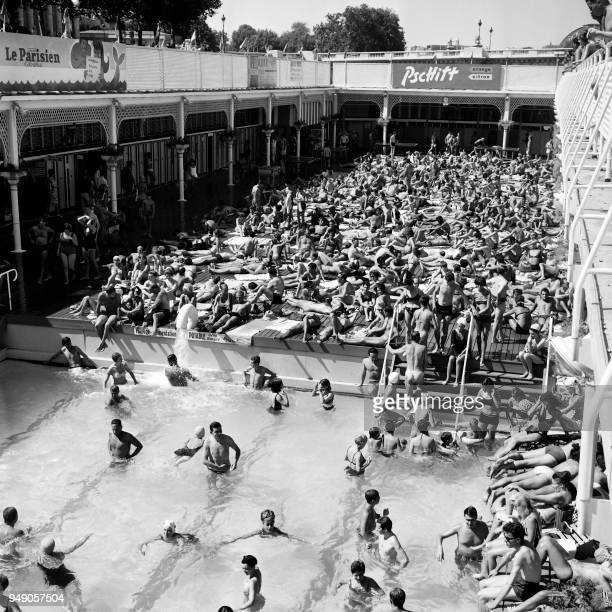 People enjoy the sun during a heat wave close at the Deligny swimming pool on the banks of the Seine in Paris on August 71964