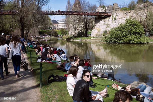 People enjoy the sun in the ButtesChaumont Park on April 14 2013 in Paris AFP PHOTO / FRED DUFOUR