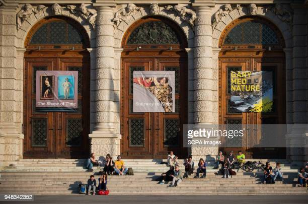 People enjoy the sun light in front of the Museum of Fine Arts in Vienna