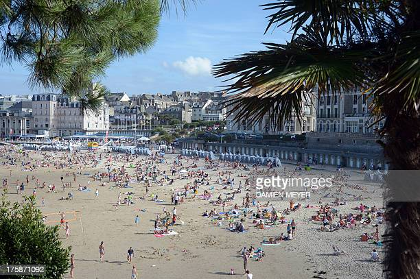 People enjoy the sun on a beach in Dinard, western France, on August 9, 2013. AFP PHOTO / DAMIEN MEYER