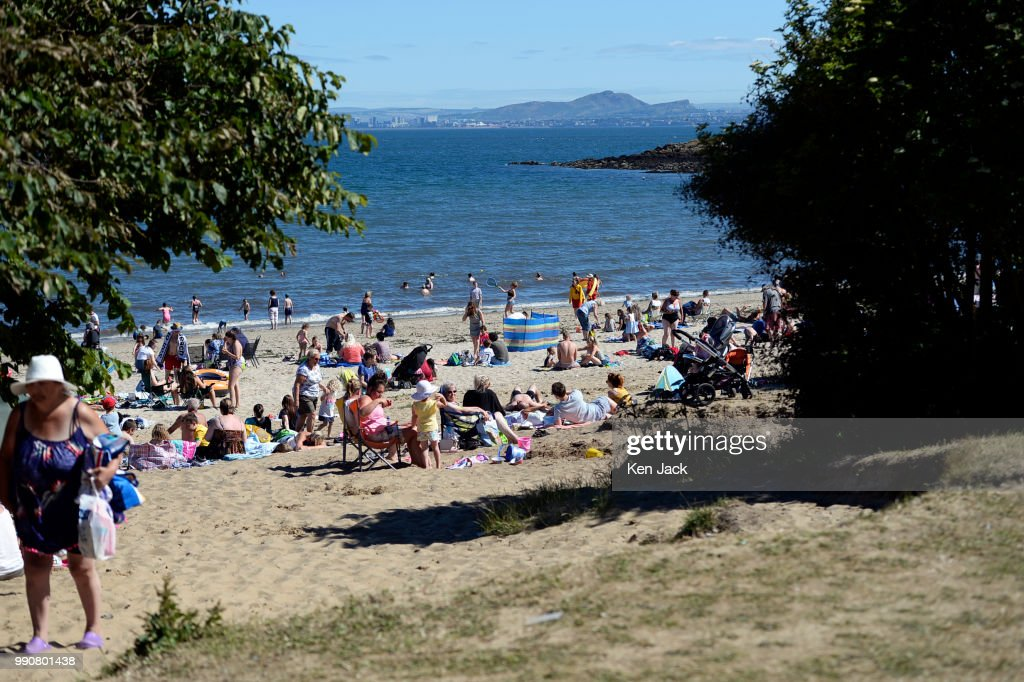 People enjoy the sun on Silver Sands beach at the start of the Scottish school holidays as the heatwave continues, with Edinburgh in the background across the Firth of Forth, on July 3, 2018 in Aberdour, Scotland.