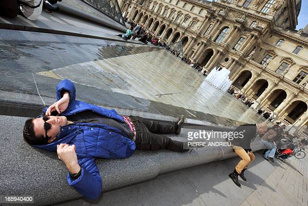 """People enjoy the sunny spring weather at the """"Cour Carree"""" of the Louvre Museum on April 7, 2013 in Paris, after weeks of unusual cold weather..."""