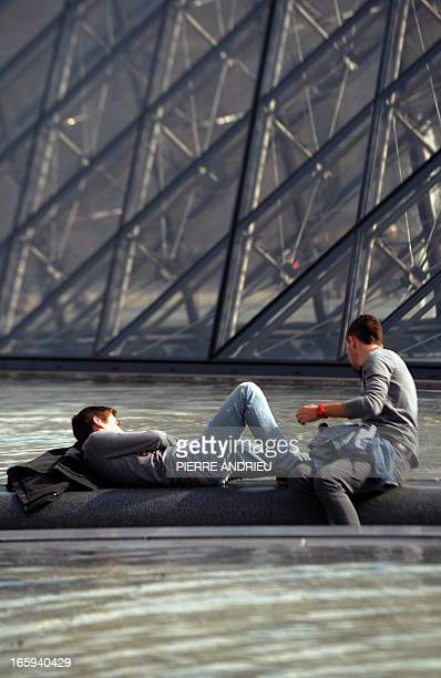 """People enjoy the sunny spring weather by the fountains at the """"Cour Carree"""" of the Louvre Museum on April 7, 2013 in Paris, after weeks of unusual..."""