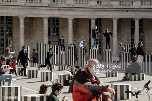 People enjoy the sunny weather by the Colonnes de Buren, in the gardens of the Palais Royal gardens, in Paris, on February 23, 2021. / RESTRICTED TO...