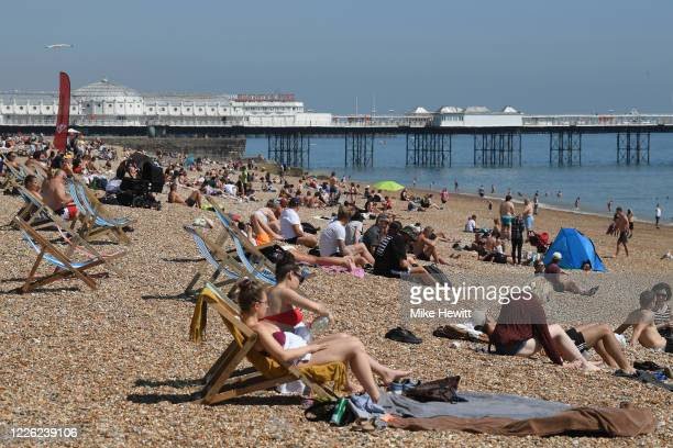People enjoy the sunny weather on Brighton beach on May 21 2020 in Brighton England The British government has started easing the lockdown it imposed...