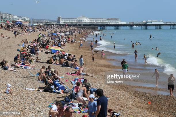 People enjoy the sunny weather on Brighton beach on May 25 2020 in Brighnton England The British government has started easing the lockdown it...