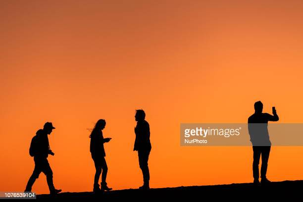 People enjoy the sunset during the first day of the new year on Venice Beach in Los Angeles California on January 1 2019
