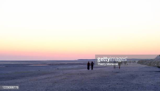 People enjoy the sunset on the beach at low tide on June 24 2020 in Le Crotoy France Le Crotoy is located on the north shore at the bottom of the...