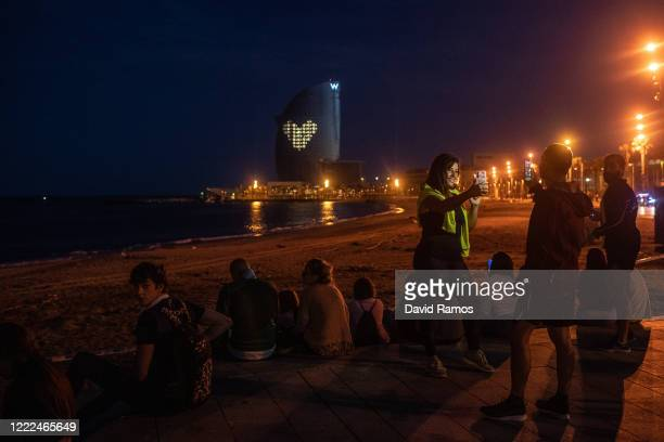 People enjoy the sunset with windows lights of the W Hotel in the background illuminated in the shape of a heart on La Barceloneta Beach on May 02,...