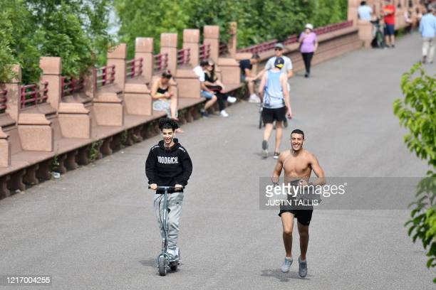 People enjoy the sunshine as they exercise in Battersea Park, near the River Thames in London on June 2 as warm weather continues during the...