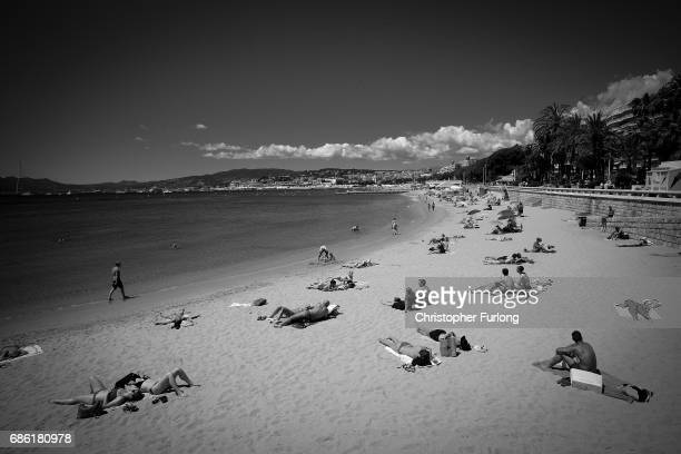 People enjoy the sunshine as they lay on the beach on the Boulevard de la Croisette during the annual Cannes Film Festival at Palais des Festivals on...