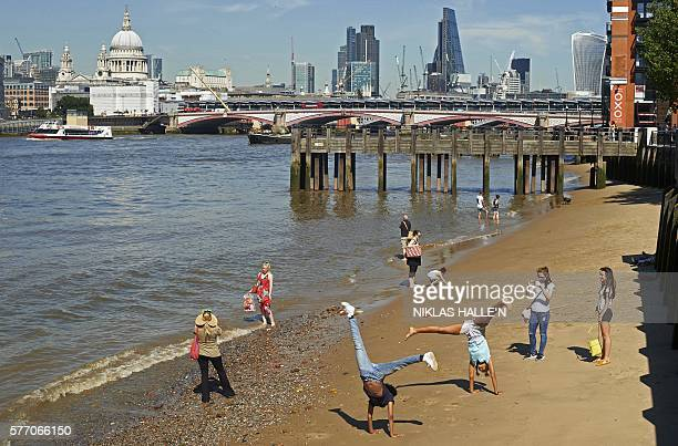 People enjoy the sunshine as they play on the south bank of the River Thames in London on July 18 backdropped by a view of the City of London skyline...