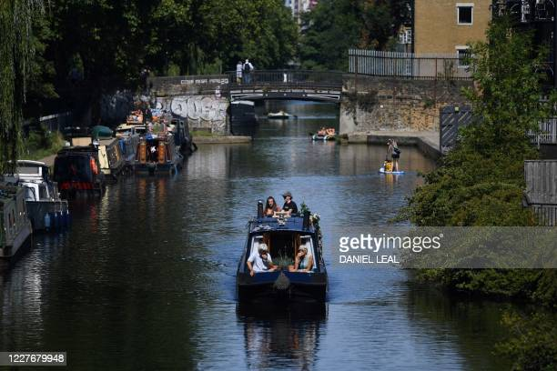 People enjoy the sunshine as they travel on a narrow boat along Regent's Canal, near Victoria Park in east London, on July 18, 2020.
