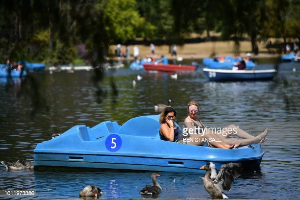 People enjoy the sunshine as they use a pedalo on the Serpentine lake in Hyde Park in west London on August 6 2018 Britain has been in the grip of...